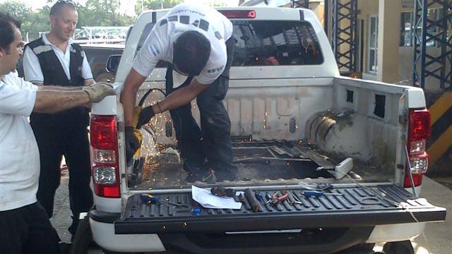 """Personal de Aduanas trabaja para """"descubir"""" la droga camuflada en la camioneta."""