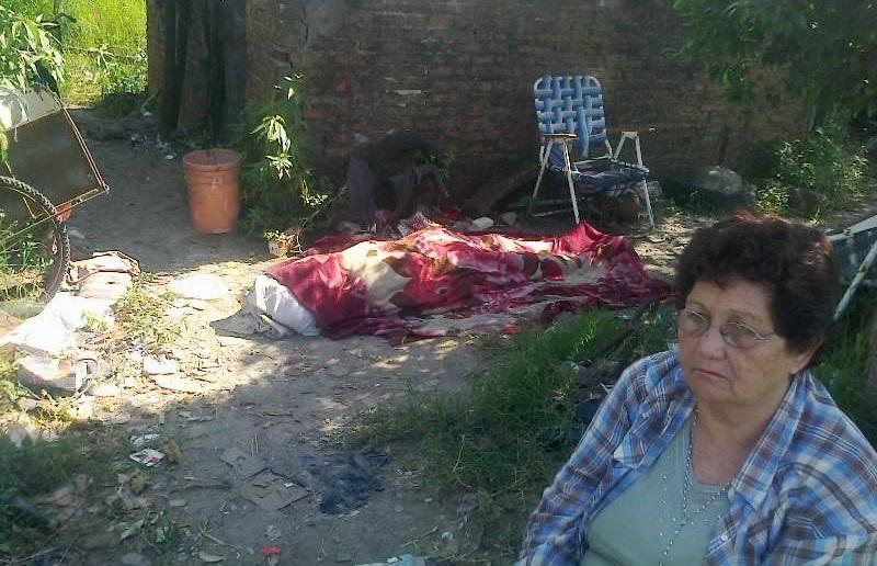 La esposa de don Sánchez esperando ayuda social. Atrás, el cuerpo sin vida de su compañero de vida.